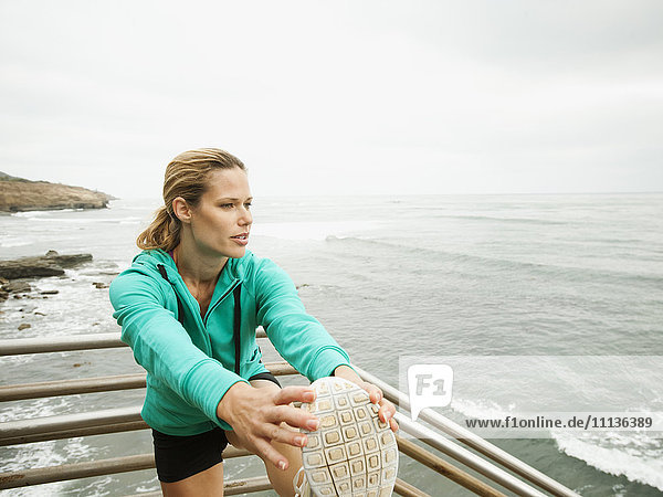 Caucasian woman stretching before exercise next to ocean