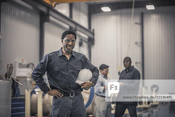 African American worker standing in factory