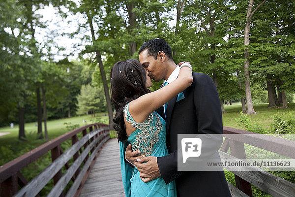 Indian wedding couple kissing on bridge