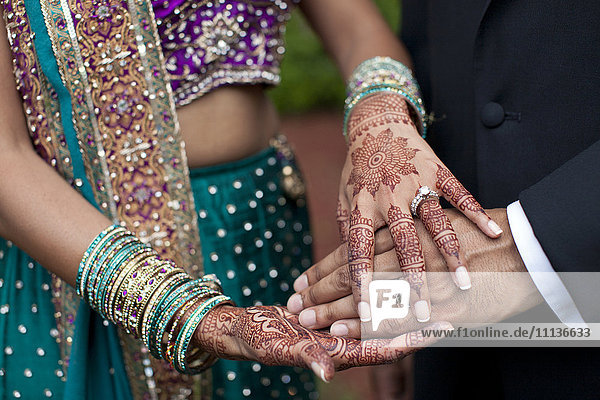 Indian wedding couple with ornate hand decorations