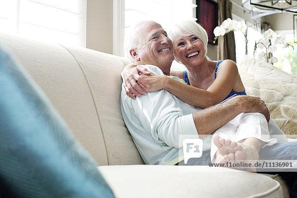 Caucasian couple hugging on sofa Caucasian couple hugging on sofa