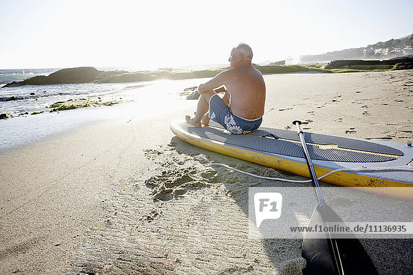 Caucasian man sitting on paddleboard