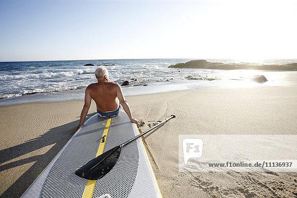 Caucasian man sitting on paddleboard Caucasian man sitting on paddleboard