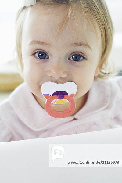 Baby girl sucking pacifier