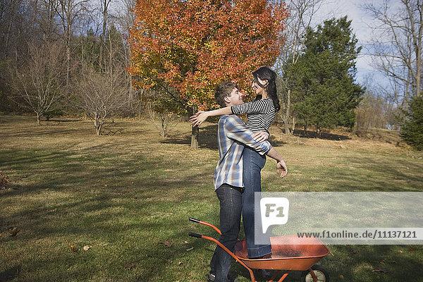 Caucasian man hugging girlfriend in yard