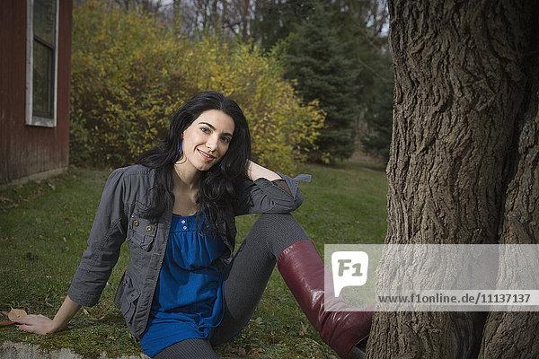 Caucasian woman sitting in yard near tree