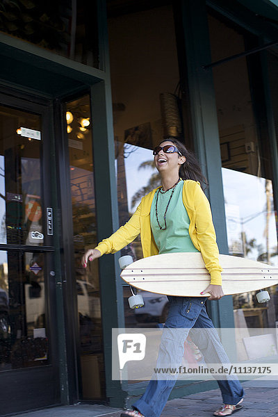 Mixed race woman carrying skateboard