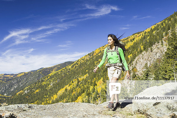 Mixed race woman hiking on rocky hilltop