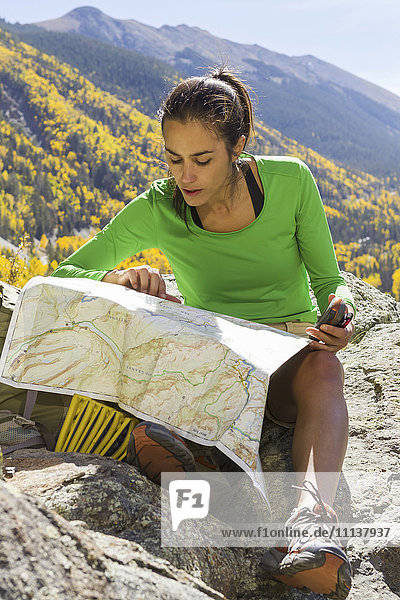 Mixed race woman reading map on rocky mountain