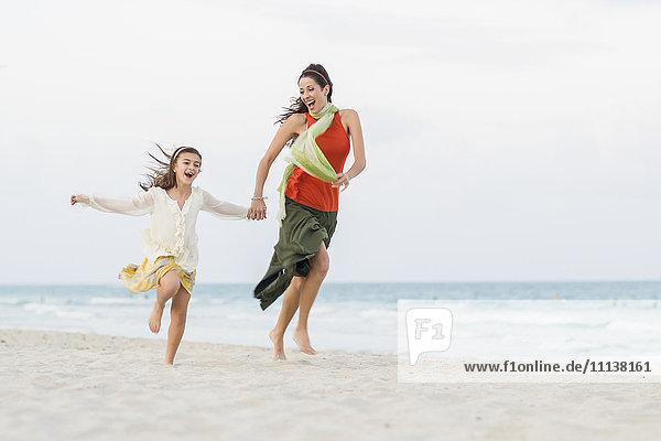 Hispanic mother and daughter running on beach