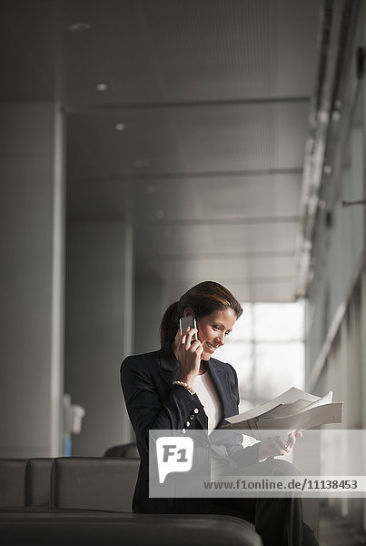 Caucasian businesswoman holding paperwork and talking on cell phone