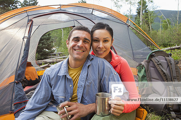 Smiling couple camping together