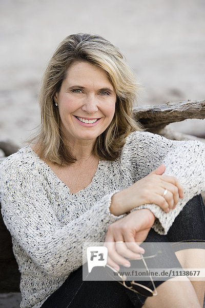 Caucasian woman sitting on beach
