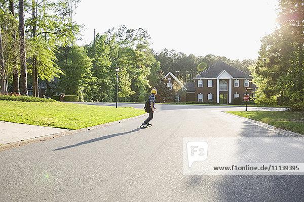 Caucasian boy skateboarding on road
