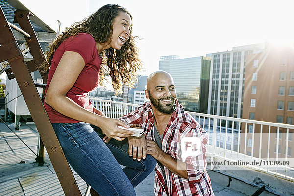 Couple relaxing on urban rooftop