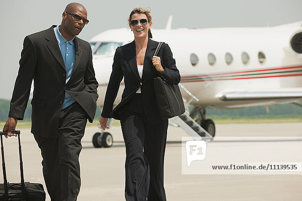 Business people walking on airport tarmac