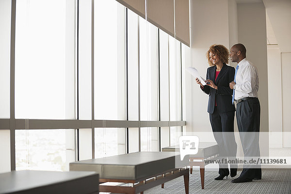 Business people talking together near window