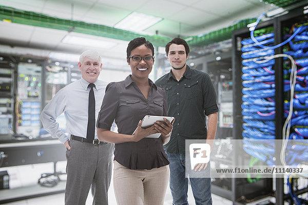 Business people standing in server room