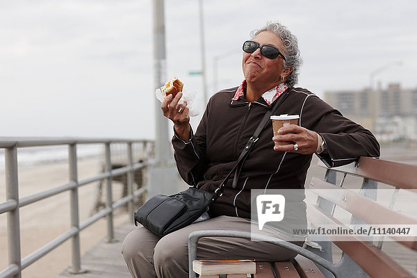 Women eating pastry and drinking coffee on boardwalk