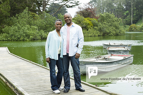 Smiling African American couple standing on pier at lake
