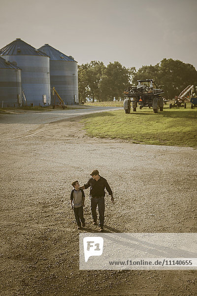 Caucasian father and son walking on farm