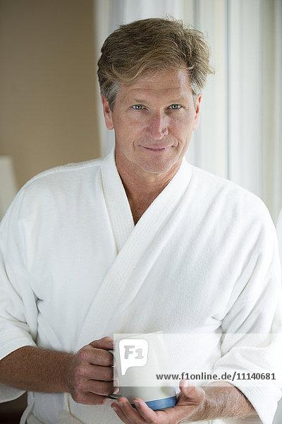 Caucasian man having coffee in bathrobe