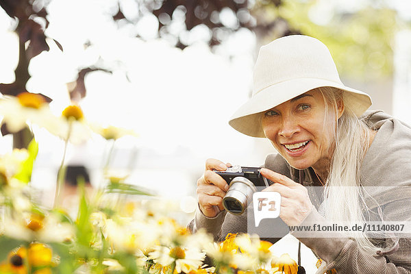 Smiling Caucasian woman photographing flowers with digital camera
