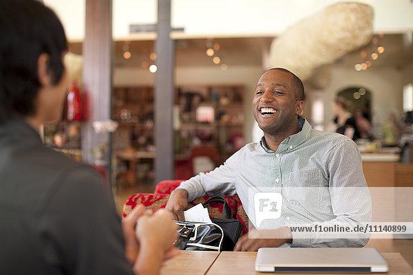 Smiling businessmen talking in cafe