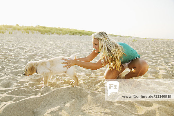 Mixed race teenage girl playing with puppy on beach