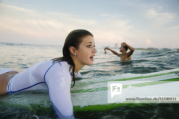 Caucasian teenage girl paddling on surfboard in ocean