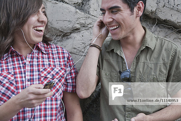 Smiling teenage boys sharing headphones and holding mp3 player