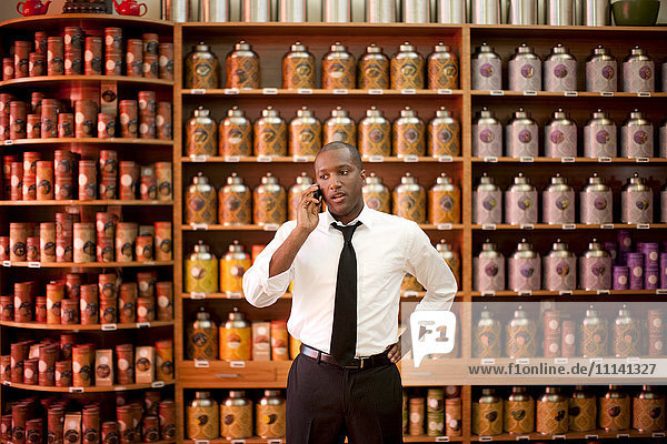 African American businessman talking on cell phone in shop