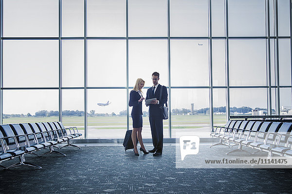 Caucasian business people standing in airport