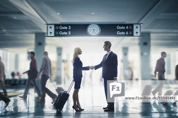 Business people shaking hands in airport