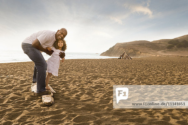 Father and daughter smiling on beach