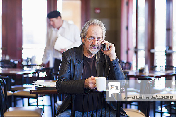 Caucasian man on cell phone in restaurant