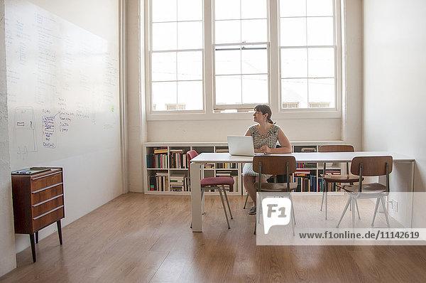 Caucasian businesswoman working on laptop in office