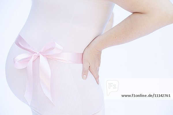 Pregnant Caucasian woman with pink ribbon around belly