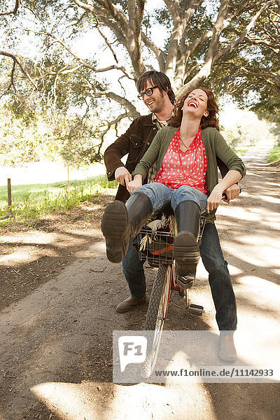 Couple riding bicycle on rural road