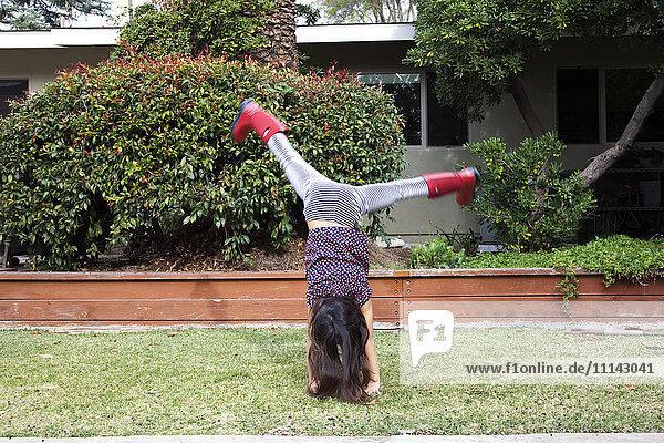 Mixed race girl doing cartwheels in backyard