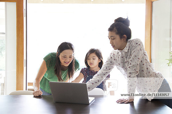 Mother and daughters using laptop in dining room
