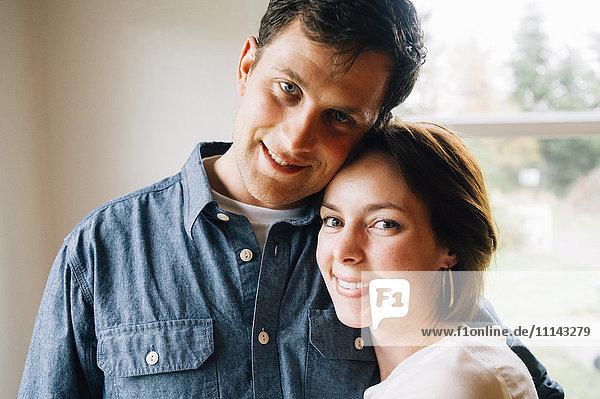 Smiling couple hugging near window