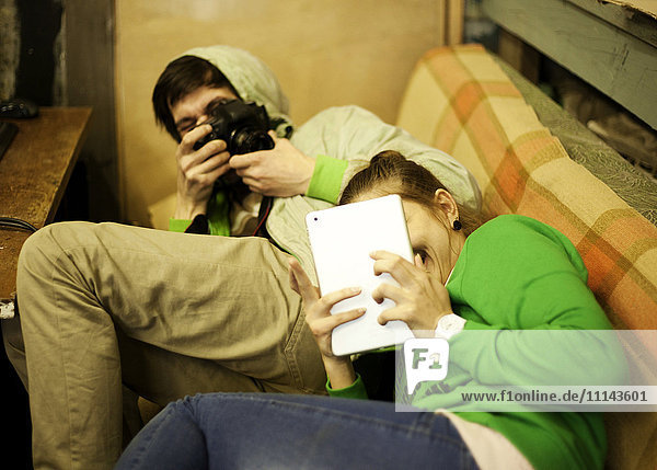 Caucasian man photographing girlfriend on sofa