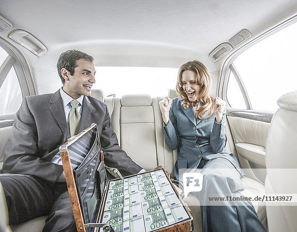 Businessman showing suitcase of money to colleague