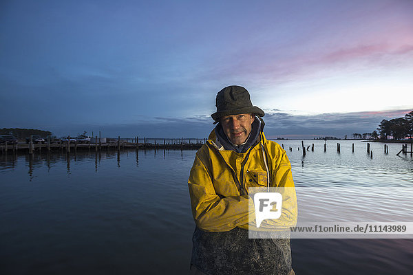 Caucasian fisherman standing by ocean