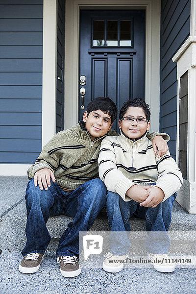 Hispanic boys hugging on front stoop