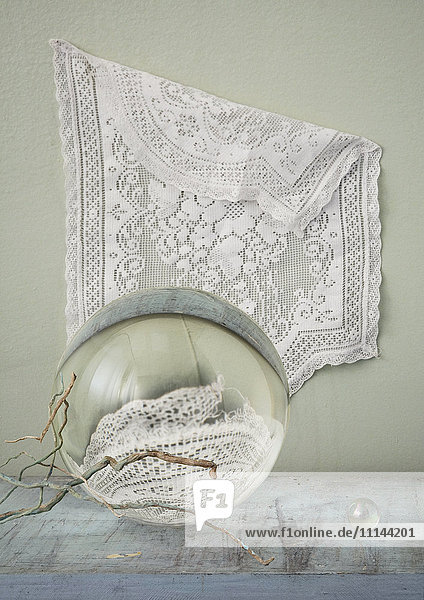 Lace hanging over crystal balls and branches on table