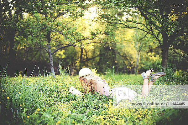 Woman reading book and laying in rural field