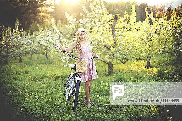 Woman pushing bicycle in rural field