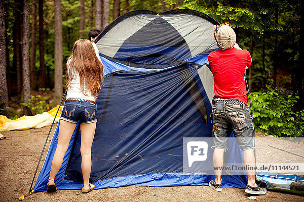 Couple setting up tent at campsite